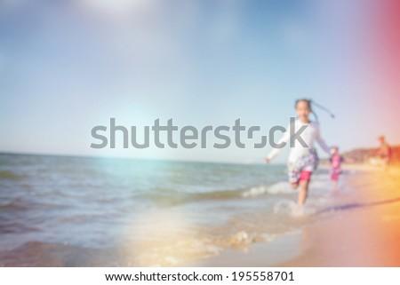 kids running at the beach, defocused image - stock photo