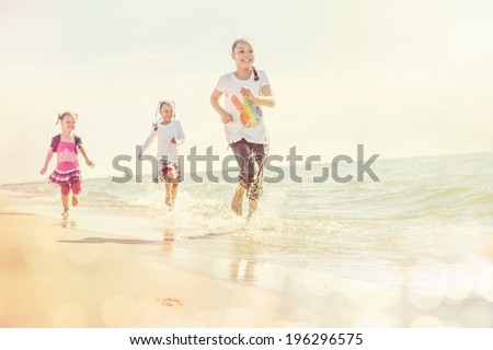 kids running at the beach, focus on beach and waves, runners have motion blur - stock photo