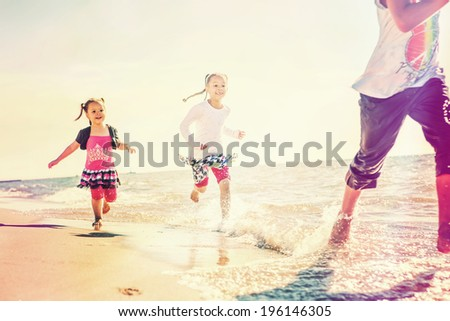 kids running at the beach, runners have motion blur - stock photo