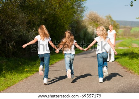 kids running down a path in spring, their mother standing in the background - stock photo