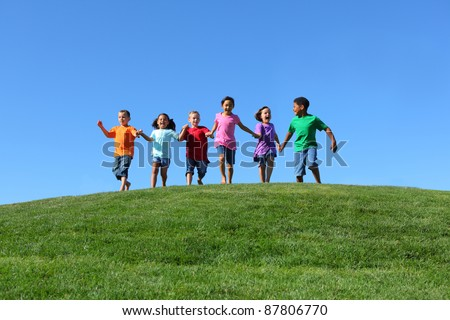 Kids running on grass hill with blue sky - stock photo