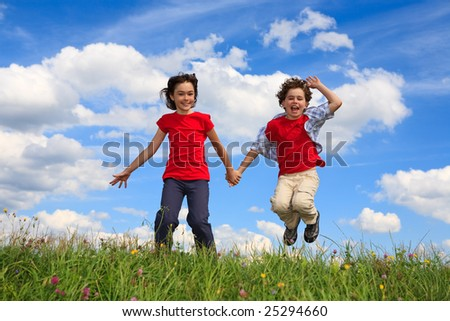 Kids running on green meadow against blue sky