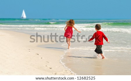 Kids running on pretty beach with sailboat  in distance - stock photo