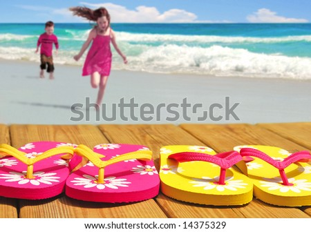 Kids running towards colorful flip flop sandals on boardwalk with ocean in distance - stock photo
