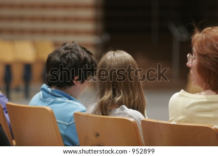 kids seated in auditorium conversing - stock photo