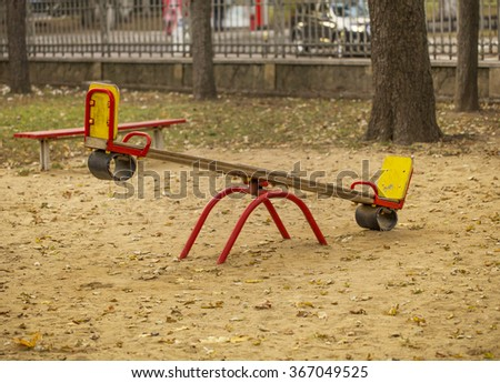 Kids seesaw on sandy playground in autumn city park. Background: fence, car, trees - stock photo
