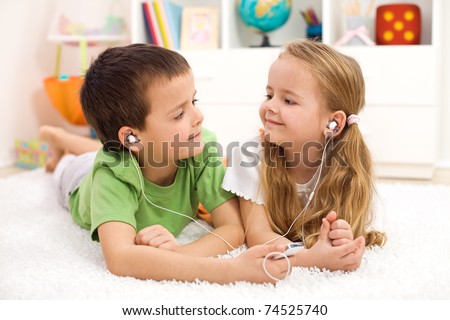 Kids sharing earphones listening to music laying on the floor - stock photo