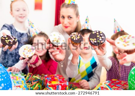 Kids showing muffin cakes into the camera at birthday party, larger group of children and mother - stock photo