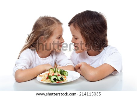 Kids sipping on the same string of pasta - sharing a plate of healthy food, isolated - stock photo