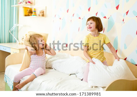 kids sisters playing on the bed indoors - stock photo