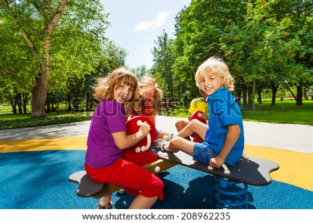 Kids sit on playground carousel and smile