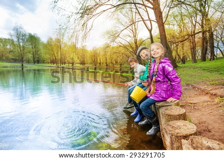 Kids sitting near pond holding fishing tackles stock photo for Stocked fishing ponds near me