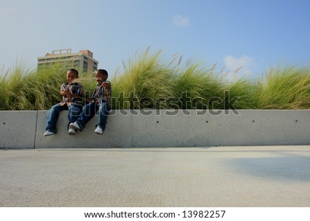 Kids Sitting on a Ledge to the Left. - stock photo