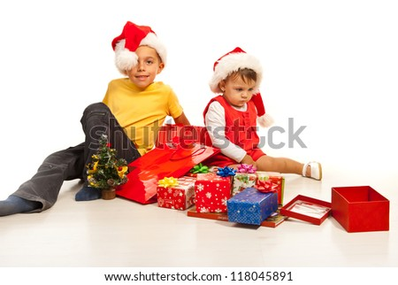 Kids sitting on florr with many Christmas gifts around them - stock photo