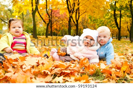 Kids sitting on ground covered with leaves - stock photo