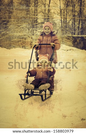 Kids skating and sledding in winter outdoors in a grunge style. - stock photo