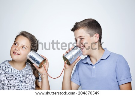 Kids speaking to a can against gray background - stock photo