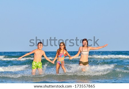 Kids splashing and playing in the sea water - stock photo