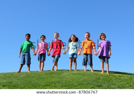 Kids standing on grass hill with blue sky - stock photo