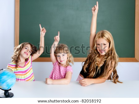 kids student clever girls group in classroom raising hand finger - stock photo