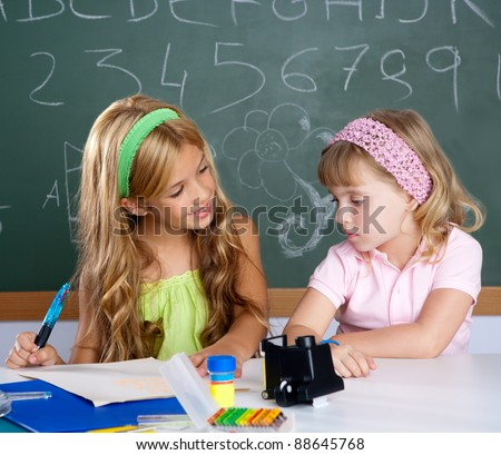 kids students in classroom helping each other at school desk - stock photo