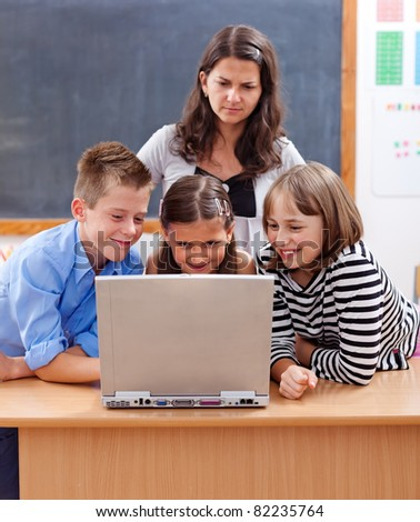 Kids surfing on the internet, watching unsafe content. Teacher stands behind and worries about