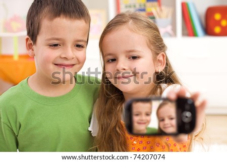 Kids taking a photo of themselves using a modern mobile phone - stock photo