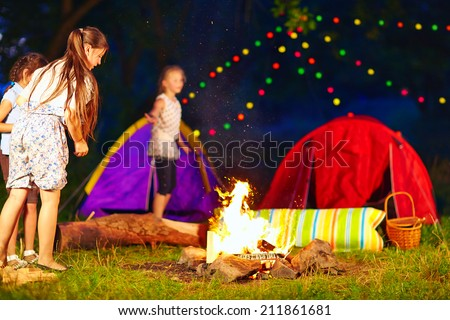 kids throwing wood in campfire, summer camp - stock photo