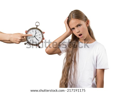 Kids time to go to bed. Portrait of mom showing daughter clock that it is late. She doesn't like that isolated white background. Face expressions, emotions. Difficult parenting concept - stock photo