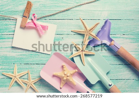 Kids tools for playing in sand  and sea object on turquoise  painted wooden planks. Place for text. Vacation, holiday, summer postcard. Toned image. - stock photo