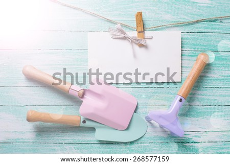 Kids tools for playing in sand and tag on clothes line in ray of light on turquoise  painted wooden planks. Place for text. Vacation, holiday, summer background.  - stock photo