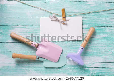Kids tools for playing in sand and tag on clothes line on turquoise  painted wooden planks. Place for text. Vacation, holiday, summer background.  - stock photo