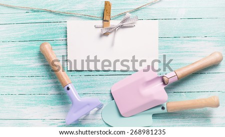 Kids tools for playing in sand and tag on clothes line on turquoise  painted wooden planks. Place for text. Vacation, holiday, summer background. Toned image.  - stock photo