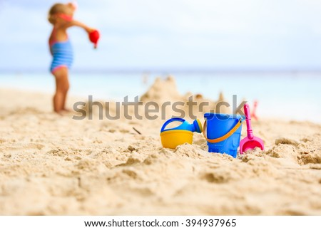 kids toys and little girl building sandcastle - stock photo