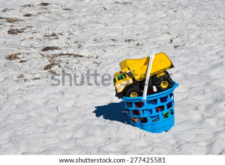 Kids Toys in a Bucket in the Sand on the Beach - stock photo