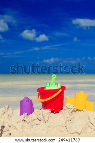 kids toys on white sand tropical beach - stock photo