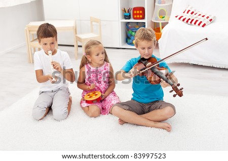 Kids trying to play on different musical instruments sitting on the floor - stock photo