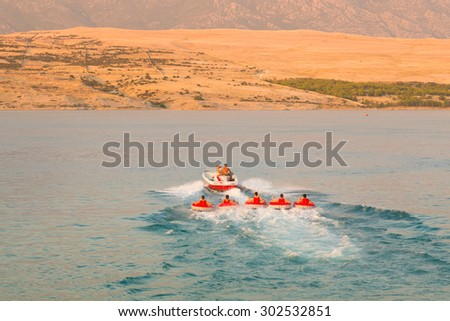 Kids tube riding tawed by speedboat on Croatian coast. Summer sea fun and adventure. Exciting water sport. - stock photo