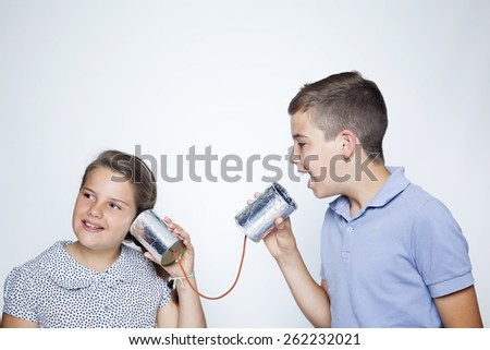 Kids using a can as telephone against gray background - stock photo