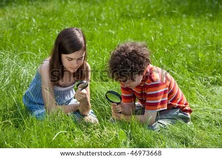 Kids using magnifying glass - stock photo