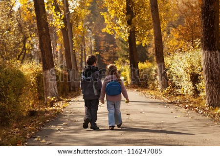 Kids walking in early autumn on sunlit park alley
