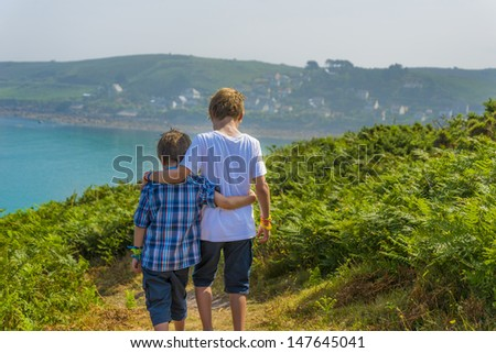 kids walking towards the sea, at a beautiful bay in normandy. - stock photo