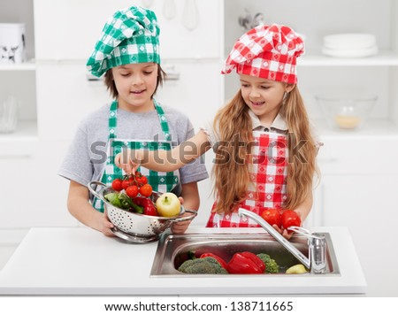 Kids washing vegetables in the kitchen putting them in a strainer