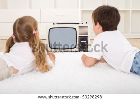 Kids watching old television set laying on the floor - stock photo