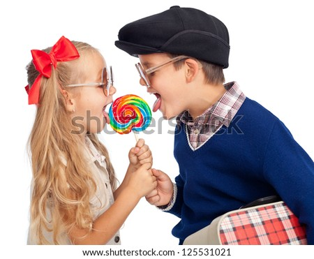 Kids wearing funny sunglasses sharing a large lollipop - isolated - stock photo