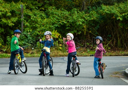 Kids wearing helmets on their bikes.  Riding on the street. - stock photo