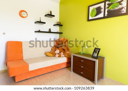 Kids white and green bedroom with orange sofa - stock photo