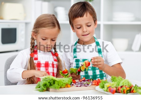 Kids with aprons preparing a healthy vegetables meal in the kitchen - stock photo