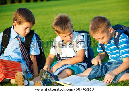 Kids with books sitting in park - stock photo