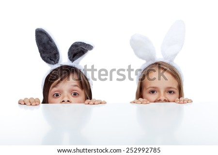 Kids with bunny ears peeking from beneath the table - waiting for the easter rabbit - stock photo